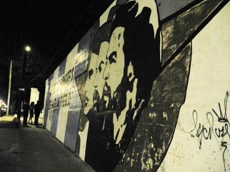 Some campaneros stroll past a propoganda mural of Che Guevara, Fidel Castro and