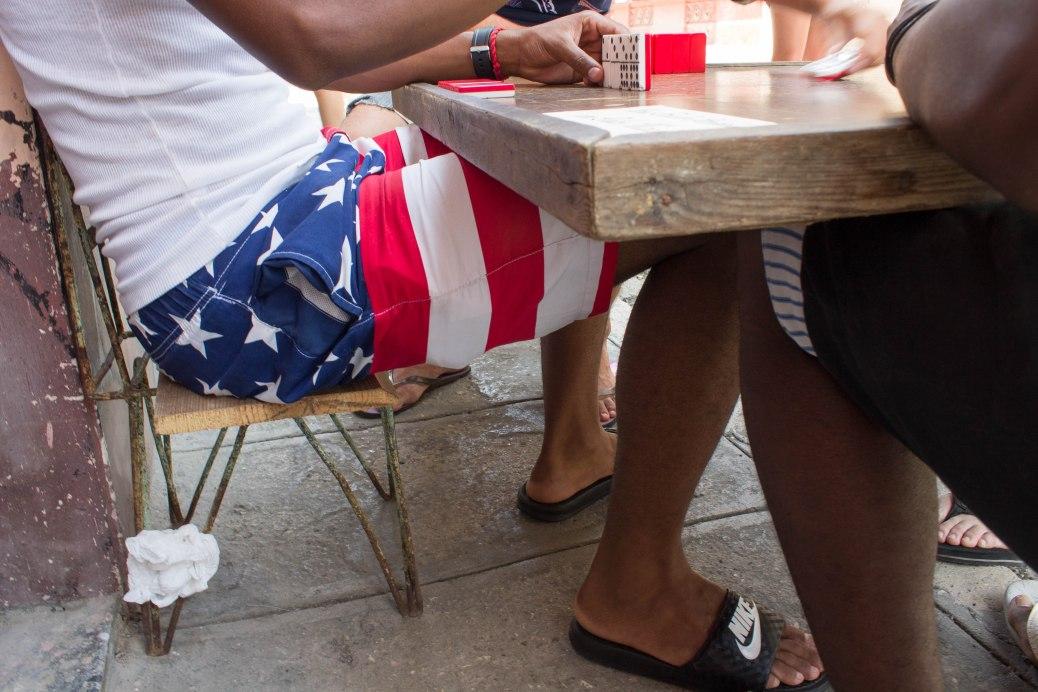 Cuban with American flag bathing suit in Havana plays dominoes